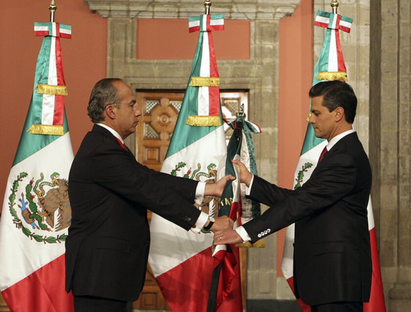 Mexico's outgoing president, Felipe Calderon, left, gives a Mexican flag to Enrique Peña Nieto during the official transfer of command ceremony at the National Palace in Mexico City.