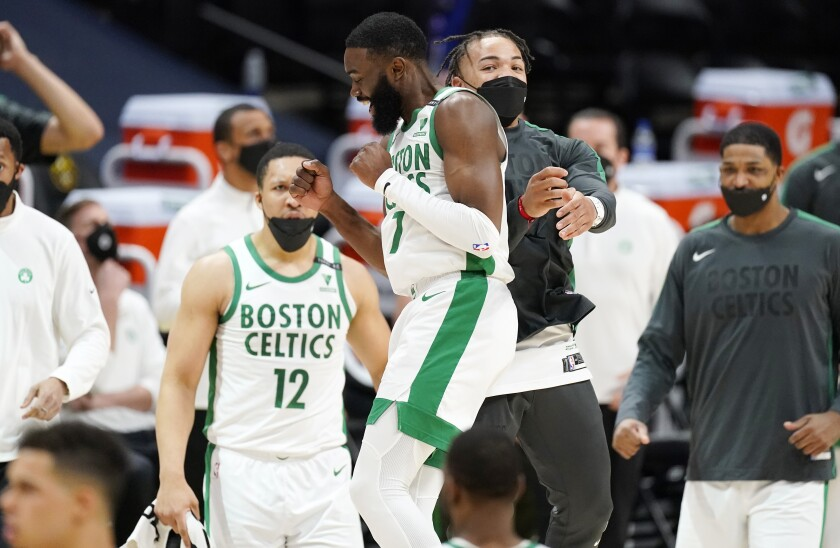 Boston Celtics guard Jaylen Brown, front left, celebrates with guard Carsen Edwards late in the second half of an NBA basketball game against the Denver Nuggets, Sunday, April 11, 2021, in Denver. (AP Photo/David Zalubowski)