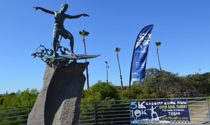 A banner next to the Cardiff Kook statue promotes the Cardiff Kook Run. Cardiff 101 Main Street has sued the run for using the statue's likeness without permission.
