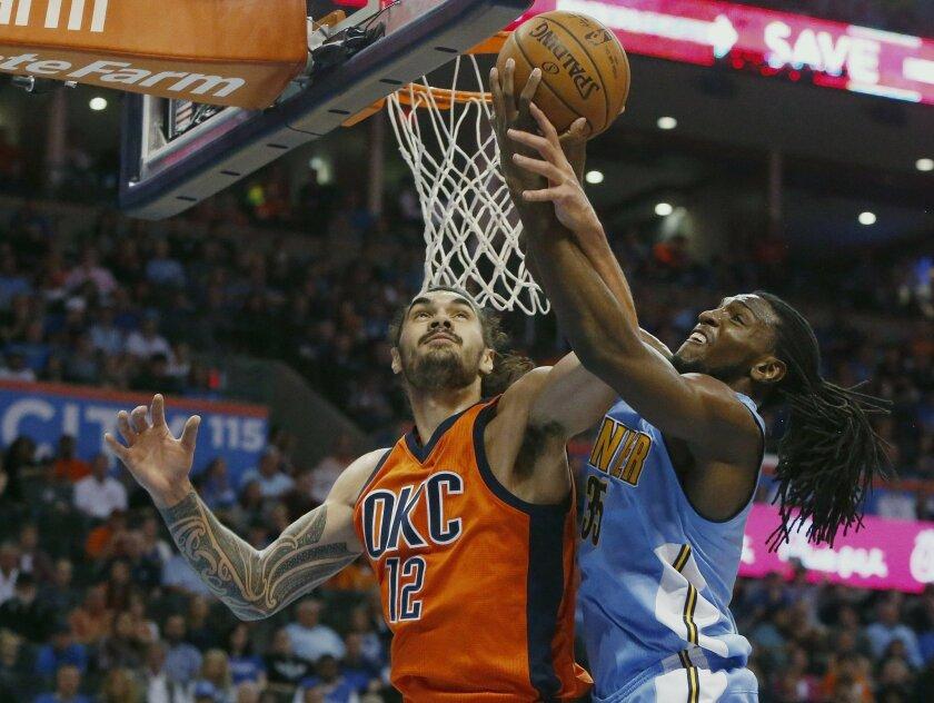 Oklahoma City Thunder center Steven Adams (12) and Denver Nuggets forward Kenneth Faried reach for a rebound in the first half of an NBA basketball game in Oklahoma City, Sunday, Nov. 1, 2015. (AP Photo/Sue Ogrocki)