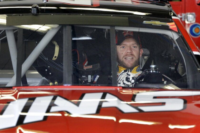 Regan Smith sits inside Kurt Busch's car before practice for the Daytona 500 NASCAR Sprint Cup series auto race at Daytona International Speedway in Daytona Beach, Fla., Saturday, Feb. 21, 2015. Smith will fill in for Busch in the wake of Busch's suspension on Friday.(AP Photo/John Raoux)