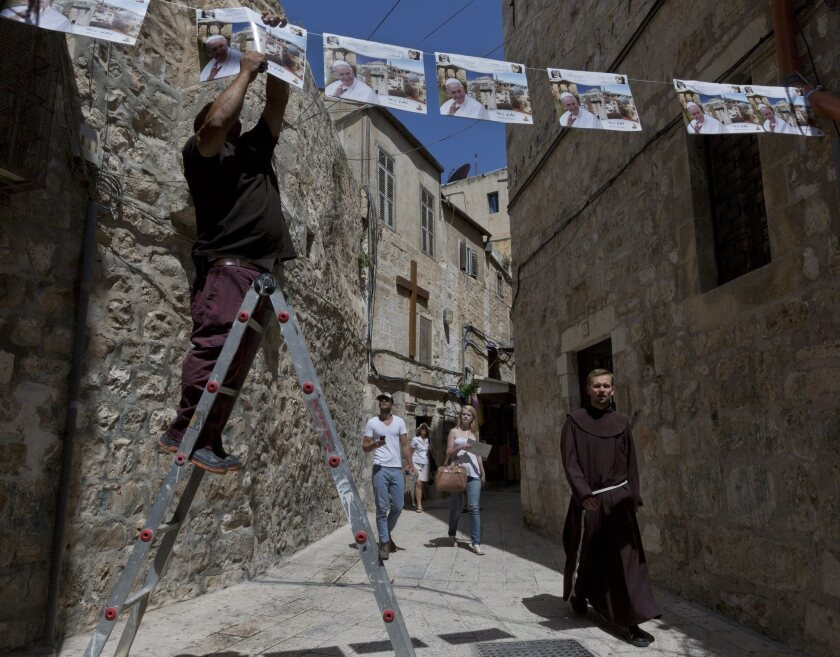 A worker hangs posters welcoming Pope Francis to Jerusalem as a Franciscan monk and some tourists walk past in the city's Christian Quarter.