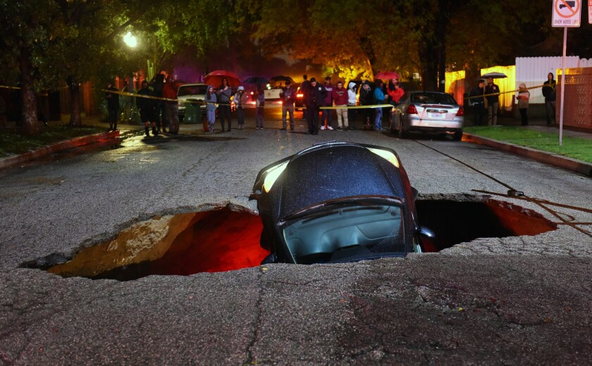 A car sits in a sinkhole on Woodbridge Street near Laurel Canyon Boulevard in Studio City in February 2017.