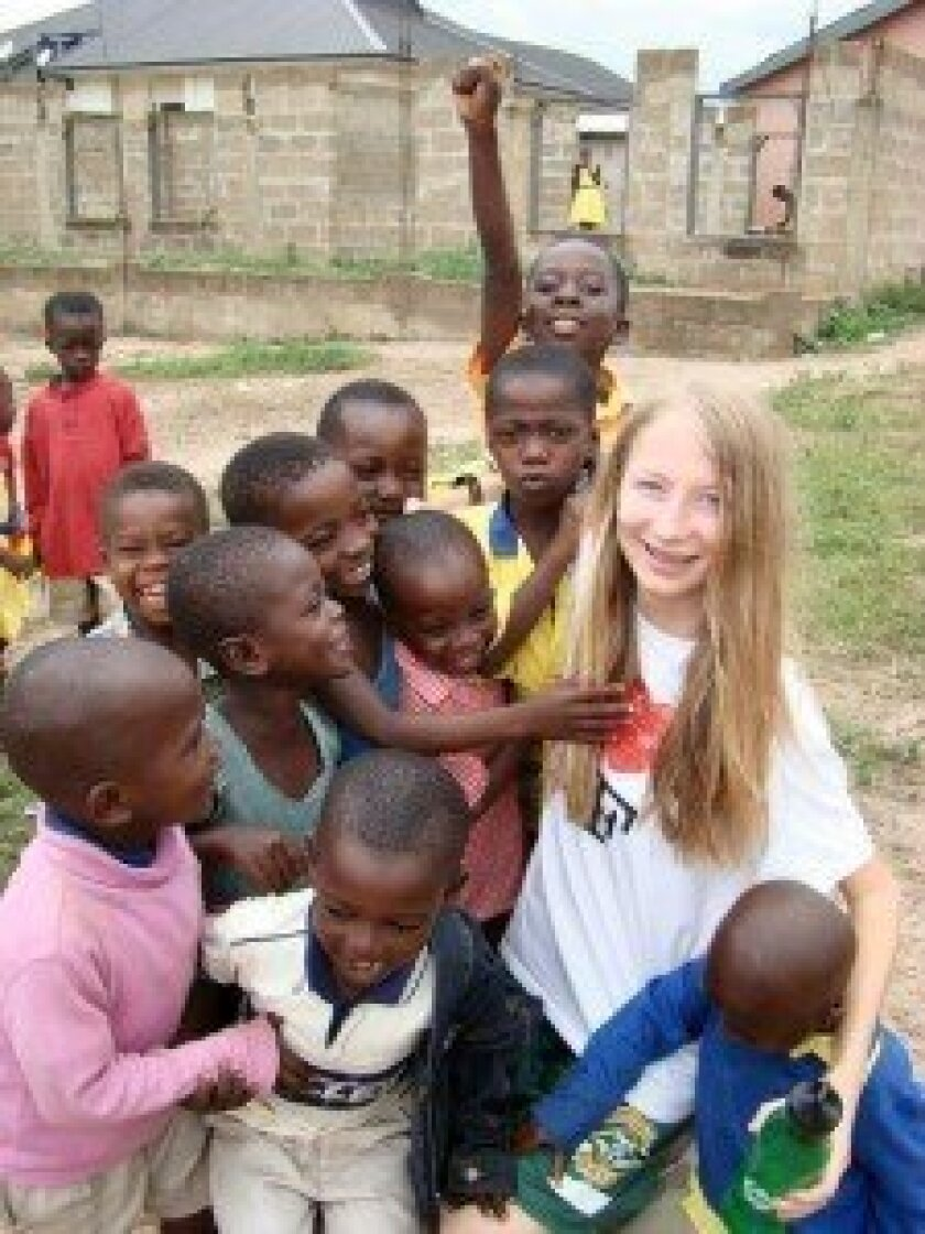Claire Bolton, CCA senior, volunteered her time to build a school in Ghana this summer with Empathy FX. The village children were fascinated by her long blonde hair. / Courtesy photo