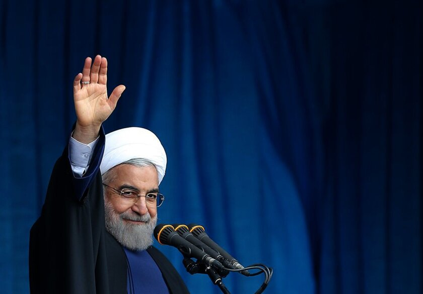 A photo provided by the office of Iranian President Hassan Rouhani shows him waving to the crowd during a public speech.