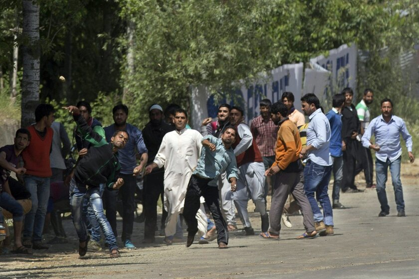 FILE - In this Friday, May 27, 2016, file photo, Kashmiri Muslim villagers throw stones at Indian security personnel in support of rebels during a gunbattle in Khonshipora, 40 kilometers (25 miles) west of Srinagar, Indian controlled Kashmir. Frustrated after decades of political stasis and militar