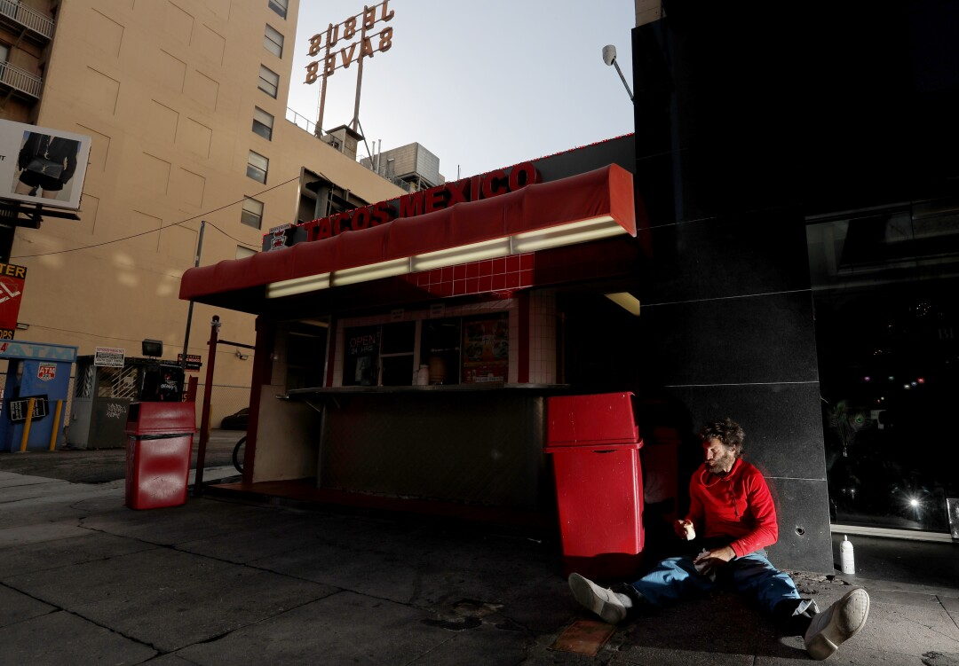A homeless man named MIke eats food fished from a trash can at a taco stand along Broadway in downtown Los Angeles