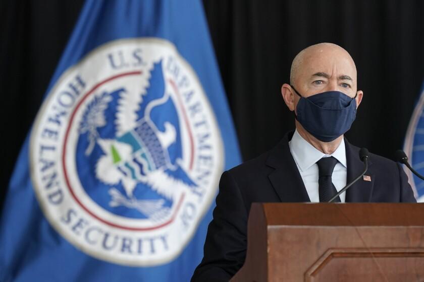 Alejandro Mayorkas speaks in front of a blue flag.