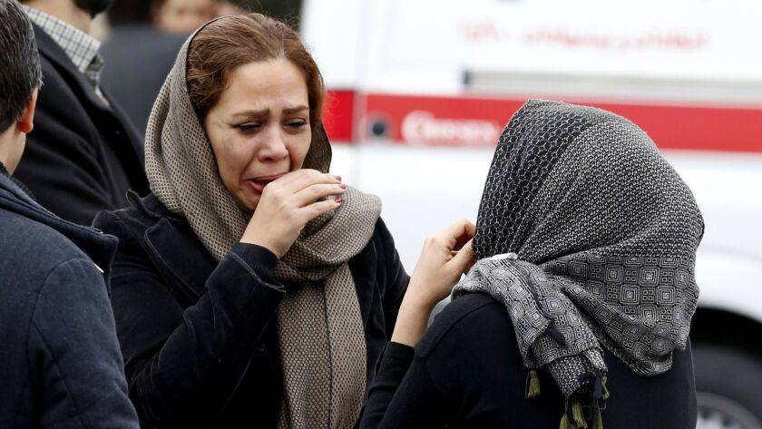 Relatives of passengers aboard Aseman Airlines Flight 3704, which crashed in the mountains of southern Iran, react outside a mosque near Tehran's Mehrabad International Airport on Feb. 18.