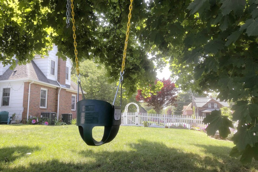 In this June 23, 2020, photo, a child's swing sits empty beneath a giant shade tree in Warwick, R.I. Associated Press journalist William J. Kole and his wife moved from Massachusetts to Rhode Island to be close to their two little grandsons, but the coronavirus pandemic forced a painful and prolonged separation. (AP Photo/William J. Kole)