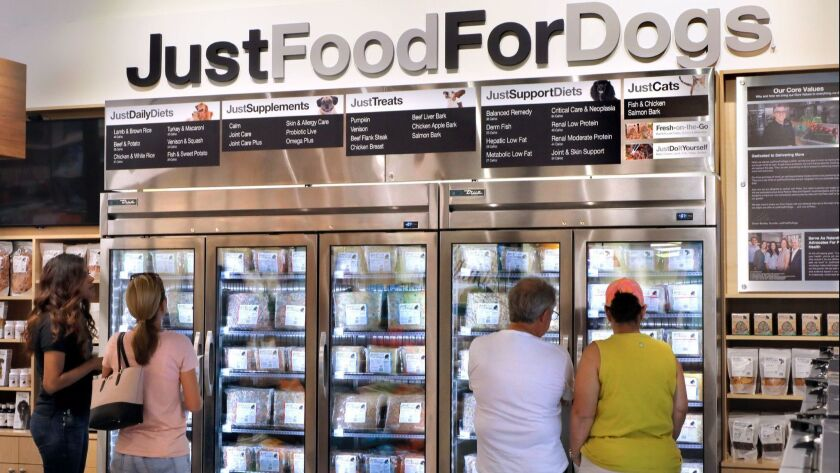 Customers in the new PetCoach store examine the extensive selection of Just Food For Dogs in a frozen food display case.
