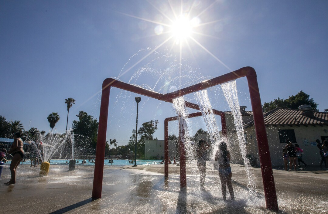 Children stand in falling water in a play area