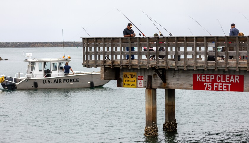 A U.S. Air Force boat passes by the small Oceanside Harbor fishing pier on Wednesday.