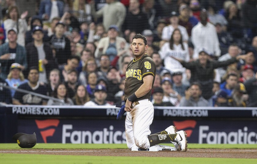 Ian Kinsler kneels at third base after he was tagged out while trying to steal third in the 10th inning against the Reds on Friday at Petco Park.