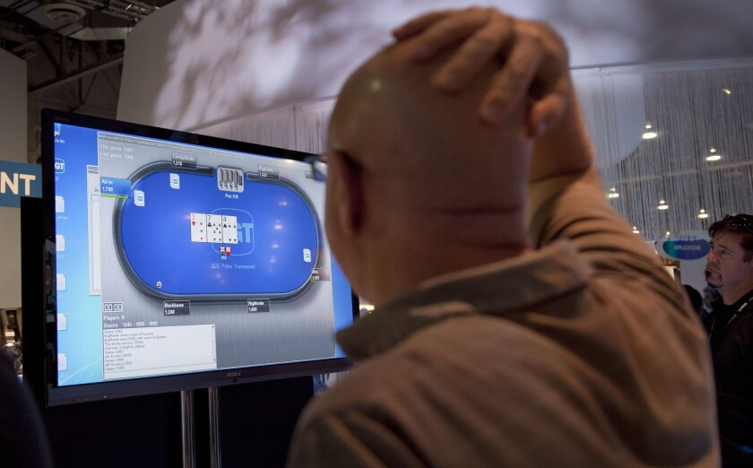 Casino industry representatives and exhibitors watch an online poker game at the industry's G2E gaming conference in Las Vegas.