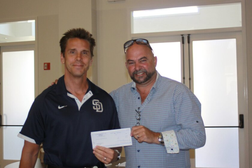 Padres Premium Plus program Manager Brad Dwight presents a check for $931 to La Jolla Village Merchants Association president Claude-Anthony Marengo.