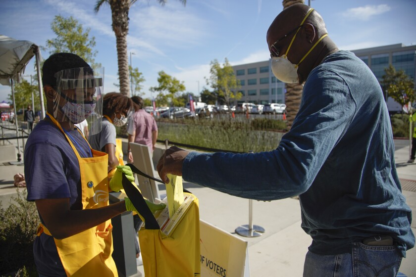 A resident drops off his mail ballot on Election Day at the San Diego County Registrar of Voters.