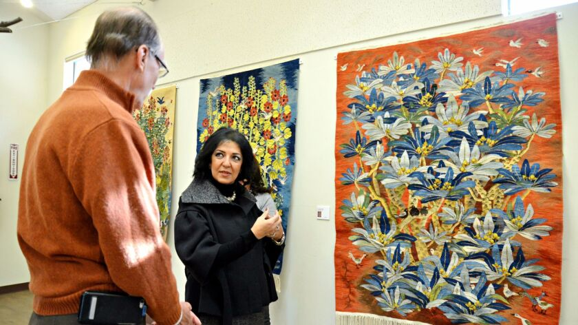 Egyptian Ambassador Lamia Mekhemar, right, discusses an Egyptian tapestry on display at the San Diego Botanic Garden with Julian Duval, president and CEO of the garden on Jan. 19.