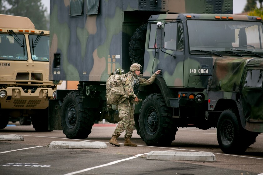 National Guard troops gather equipment from vehicles parked outside the La Mesa Civic Center Wednesday.