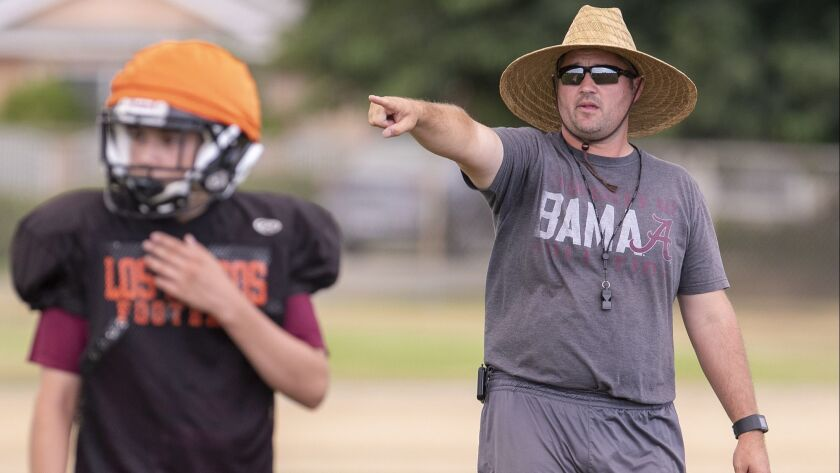 Los Amigos's head coach Carl Agnew gives directions to his players during practice on Friday, Augus