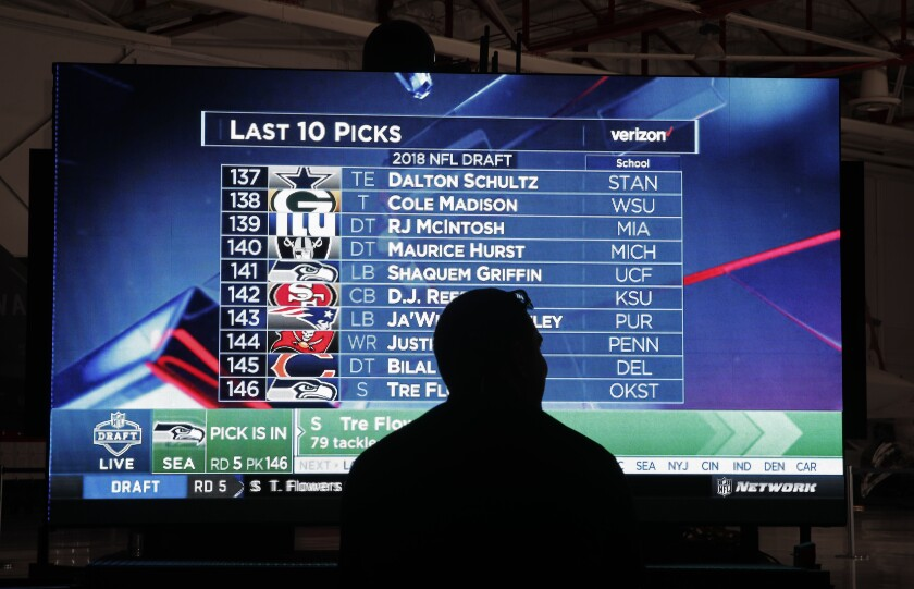 """FILE - In this April 28, 2018, file photo, a man watches the NFL draft during a Raiders draft pick event at Nellis Air Force Base, in Las Vegas. Tourism officials in Las Vegas are allocating $2.4 million to host the NFL draft in a little more than 10 weeks. The Las Vegas Convention and Visitors Authority board on Tuesday, Feb. 11, 2020, approved a budget for promotions, police, """"marquee event elements,"""" and $500,000 for contracts to be signed by the authority chief executive. (AP Photo/John Locher,File)"""