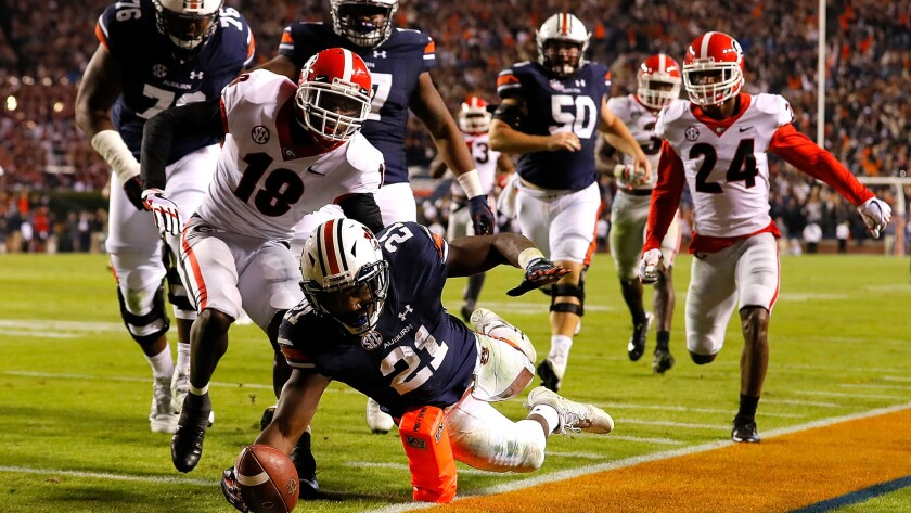 Auburn running back Kerryon Johnson dives for a touchdown past Georgia's Deandre Baker during the Tigers' upset Saturday.