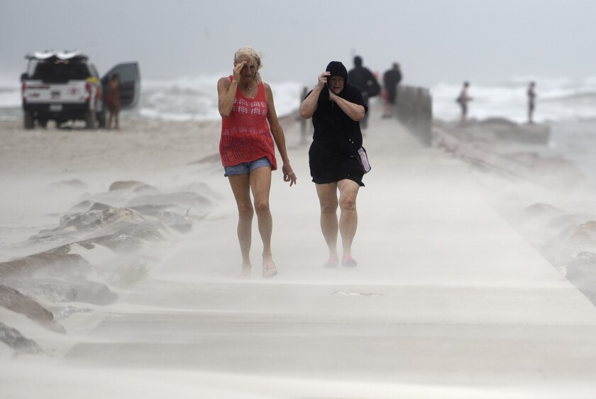 Two women walk beside a beach in a haze of sand. One holds a hand over her eyes; the other pulls up her hood.