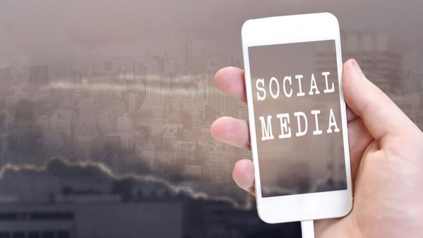 Social Media on iphone screen. Blurred business city center in the background.