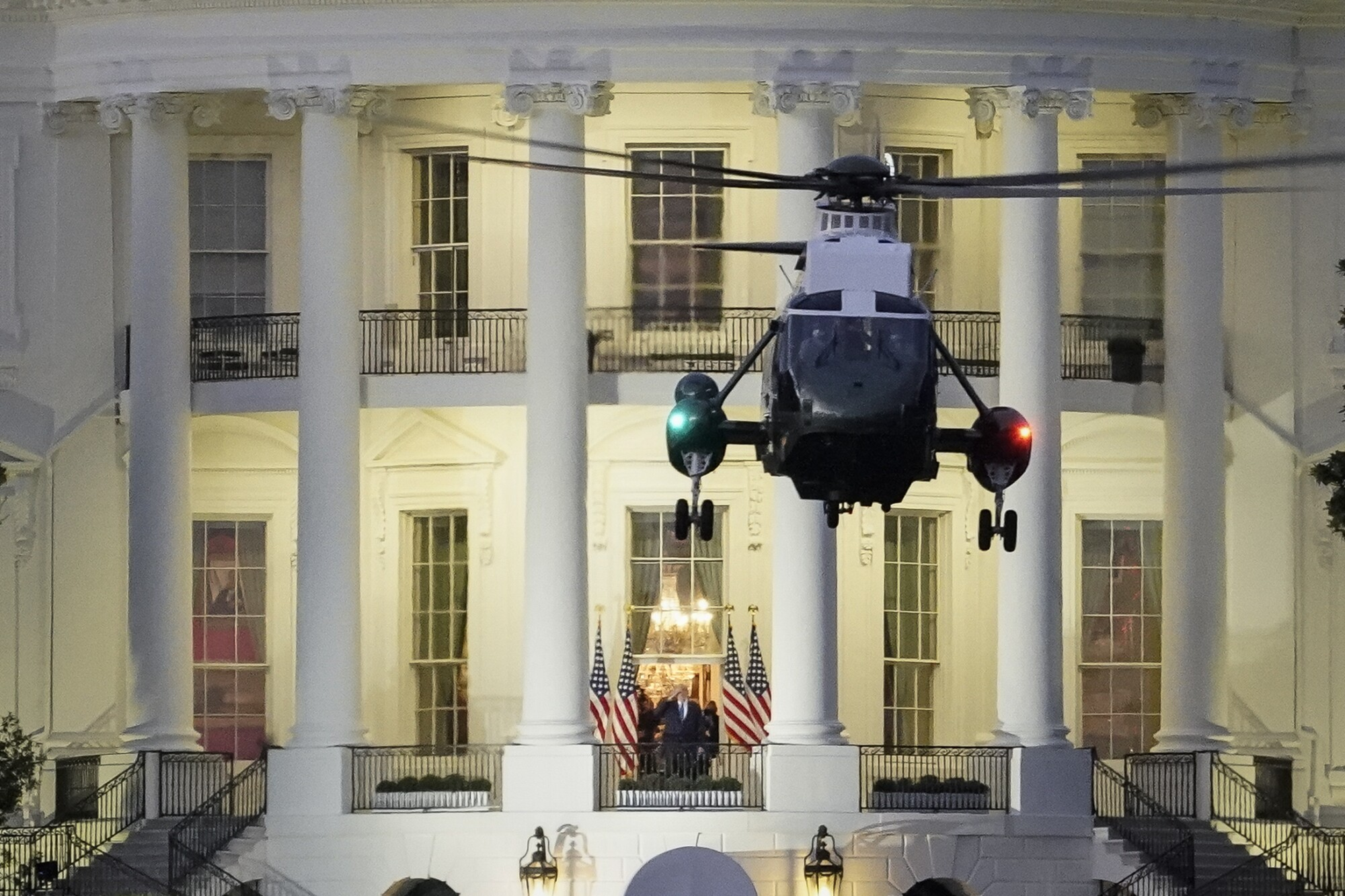 President Trump stands on the Blue Room balcony as Marine One lifts off from the White House.