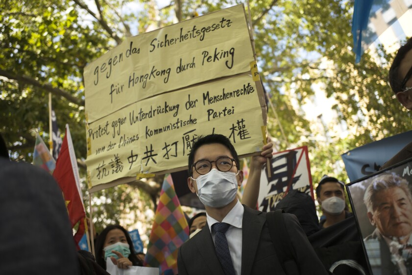 File---File picture taken Sept.1, 2020 shows Hong Kong activist Nathan Law, center, taking part in a protest during the visit of Chinese Foreign Minister Wang Yi in Berlin, Germany, (AP Photo/Markus Schreiber,file)