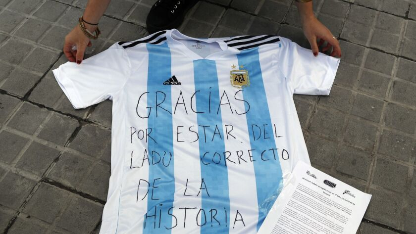 """A woman lays down an Argentina shirt with a message reading in Spanish: """"Thank you for being on the"""