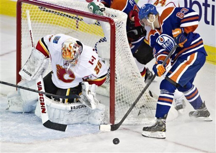 Calgary Flames goalie Joey MacDonald (35) makes the save on Edmonton Oilers Ales Hemsky (83) during second period NHL hockey action in Edmonton, Alberta, on Monday April 1, 2013. (AP Photo/The Canadian Press, Jason Franson).