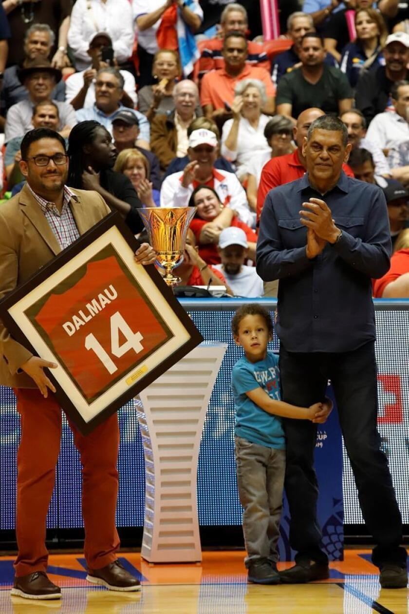El ex baloncestista Raymond Dalmau (d) recibe una camiseta enmarcada de parte del presidente de la Federación de Baloncesto de Puerto Rico Yum Ramos (i) como parte de un homenaje este lunes, antes del juego parte de la clasificación al Campeonato Mundial de Baloncesto China 2019 entre Puerto Rico y Uruguay, en el Coliseo Roberto Clemente en San Juan (Puerto Rico). EFE