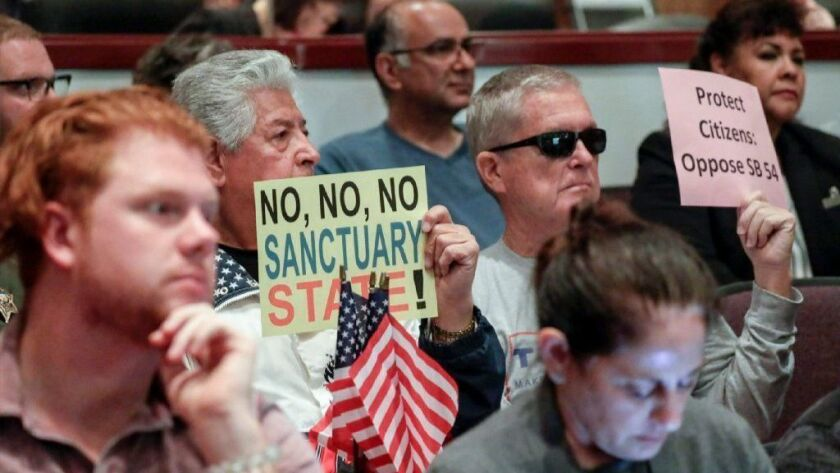 """People oppose so-called """"sanctuary state"""" laws during the Orange County Board of Supervisors meeting in Santa Ana on Tuesday. Huntington Beach is scheduled to discuss its potential opposition to the laws on Monday."""