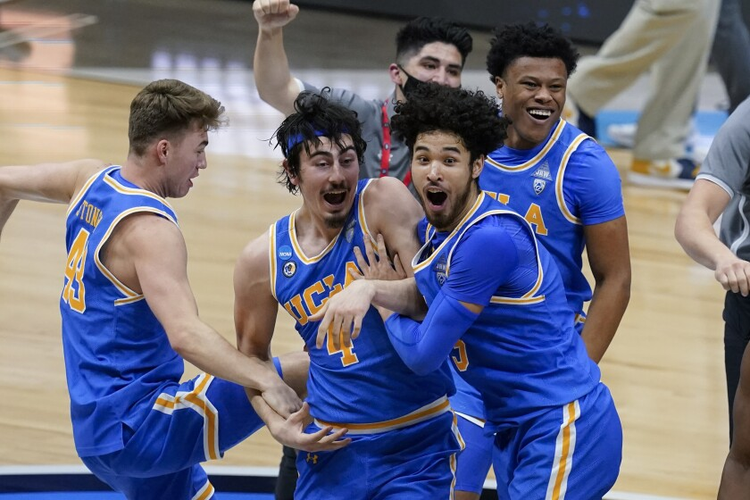 UCLA players celebrate after an Elite 8 game against Michigan in the NCAA men's college basketball tournament.