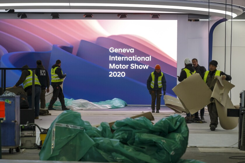 Workers dismantle a booth after that the 90th Geneva International Motor Show (GIMS) is cancelled by Swiss authorities, at the Palexpo in Geneva, Switzerland, Friday, Feb. 28, 2020. The 90th edition of the International Motor Show, scheduled to begin on March 5th, is cancelled due to the advancement of the (Covid-19) coronavirus in Switzerland. The Swiss confederation announced today that all events involving more than 1,000 people would be banned until 15 March. (KEYSTONE/Salvatore di Nolfi)