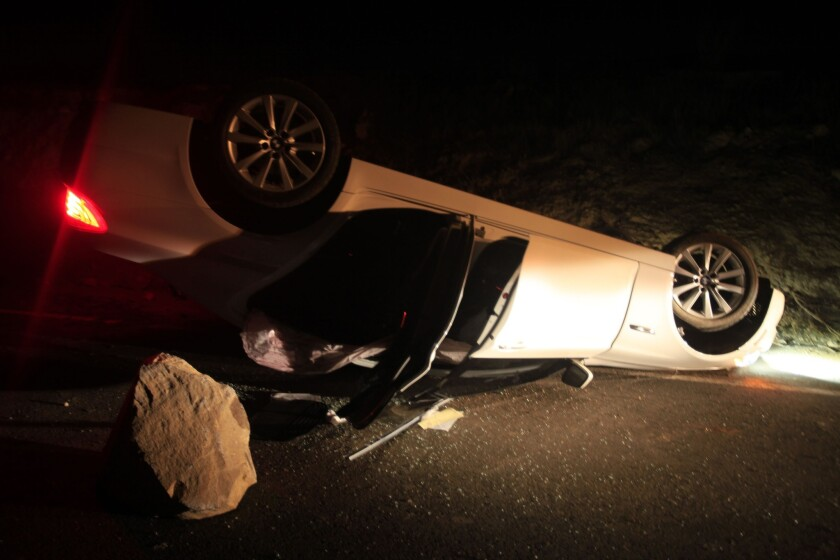 A BMW is damaged from a rock slide in Carbon Canyon after a 5.1 earthquake. The road was closed because of the risk of an aftershock.