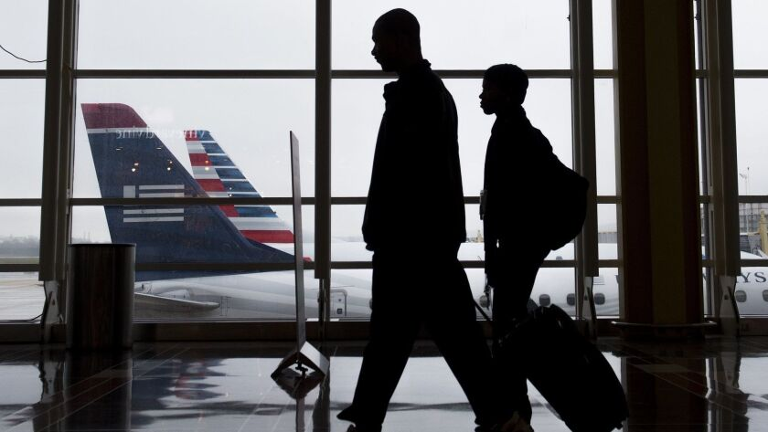 Passengers walk through a terminal at Reagan National Airport in Arlington, Va. The Global Business Travel Assn. predicts spending on business travel will surge this year, but it could slow down next year because of rising interest rates and trade wars.