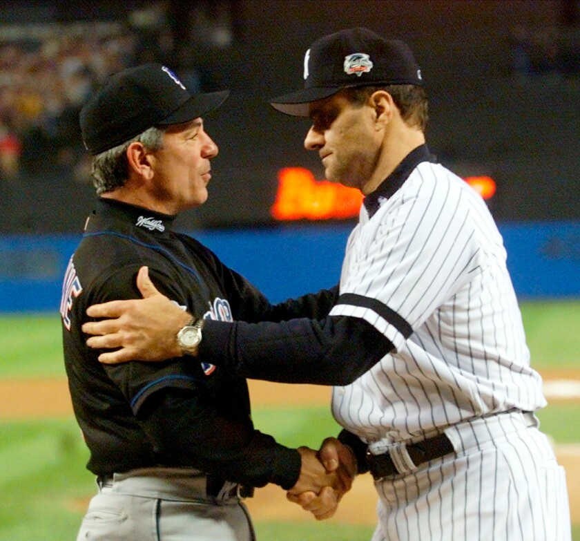 FILE - In this Oct. 21, 2000, file photo, New York Yankees manager Joe Torre, right, greets New York Mets manager Bobby Valentine before the start of Game 1 of baseball's World Series at Yankee Stadium in New York. Sports teams will hold ceremonies Saturday, Sept. 11, 2021, to mark the 20th anniversary of the Sept. 11 terrorist attacks. Valentine, manager of the 2001 Mets, will throw a ceremonial first pitch to Torre, manager of the 2001 Yankees. (AP Photo/Mark Lennihan, Pool, File)