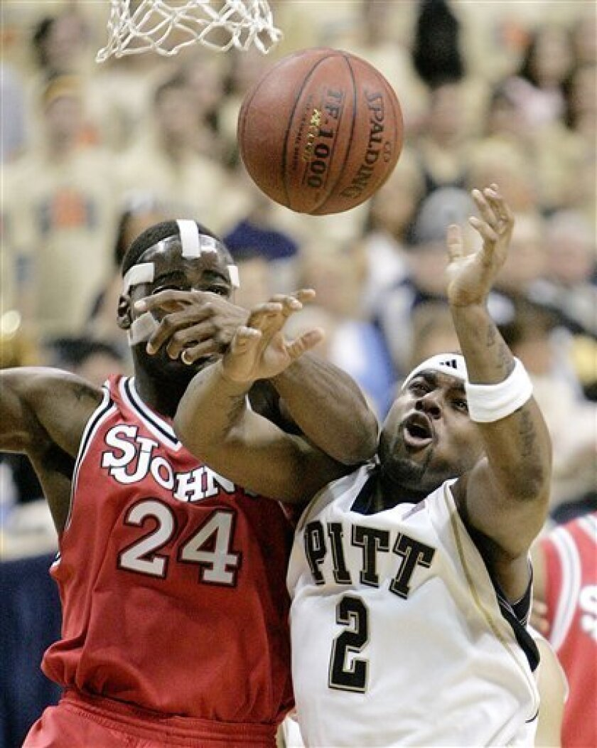 Pittsburgh's  LeVance Fields, right, is fouled by St. John's Justin Burrell as he shoots in the first half of an NCAA college basketball game in Pittsburgh, Sunday, Jan. 11, 2009. (AP Photo/Keith Srakocic)