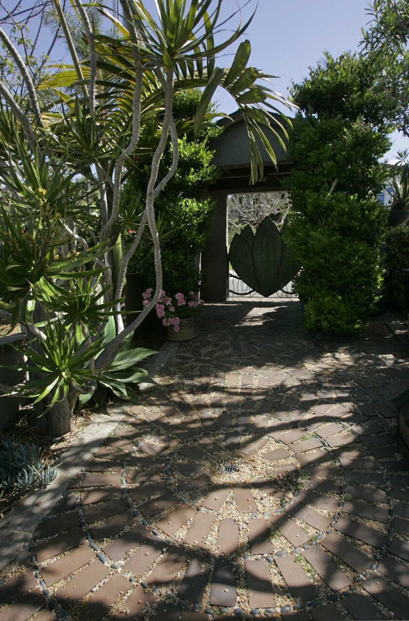 Doug Jolly and Cecilia Baetge-Jolly's garden in Leucadia features a mosaic of flagstone and rounded pebbles leading  up to a lotus gate.