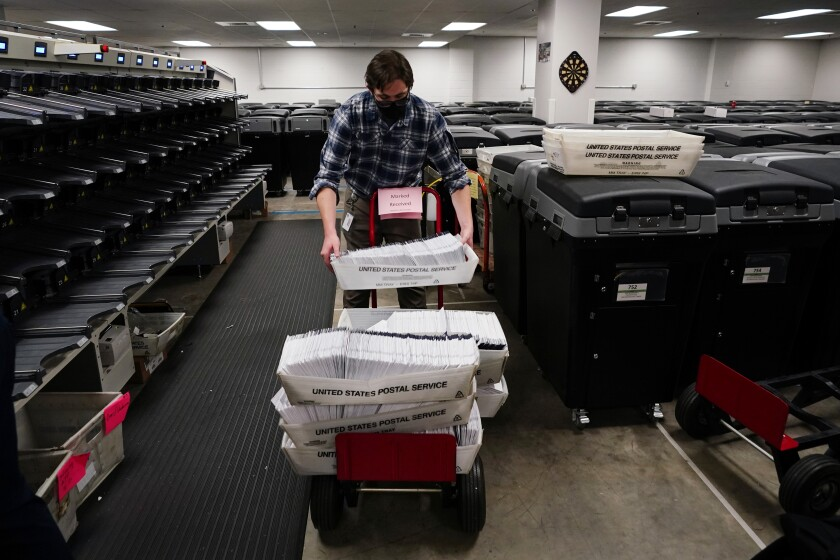 Michael Imms gathers mail-in ballots after being sorted for the 2020 General Election in the United States