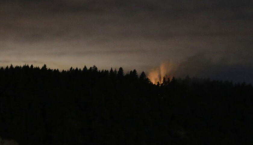 In this long-exposure photo, smoke and an orange glow are seen on Ketron Island after a stolen plane crashed.