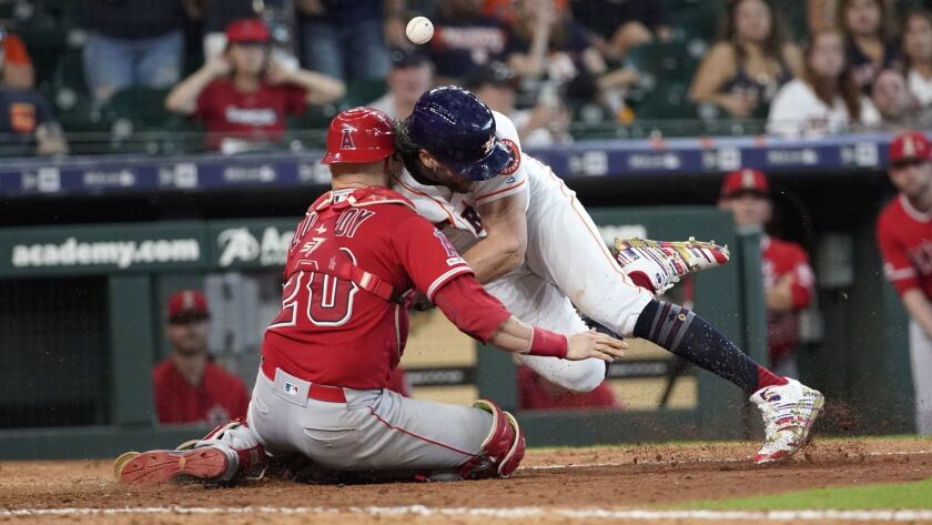 The Astros' Jake Marisnick collides with Angels catcher Jonathan Lucroy while trying to score during the eighth inning Sunday in Houston. Marisnick was called out under the home plate collision rule.