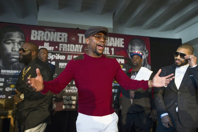 Retired professional boxer, promoter Floyd Mayweather, center, appears with boxer Ashley Theophane, right, and rapper Rick Ross, left, to promote an April 1, 2016, fight between Theophane and Adrien Broner, Monday, Feb. 29, 2016, in Washington. (AP Photo/Cliff Owen)