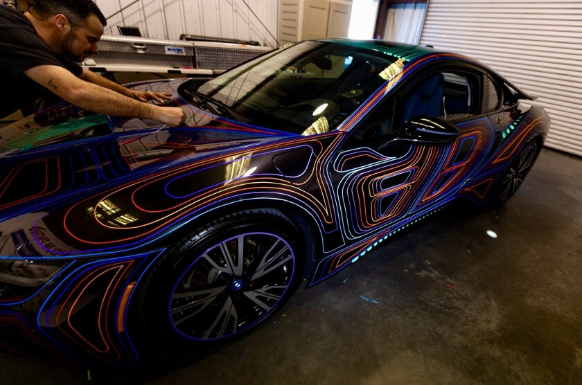 Artist Dominic Fontana works on design features on a BMW.