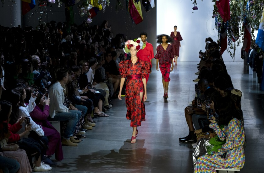 Runway models in red rose-motif looks from Prabal Gurung