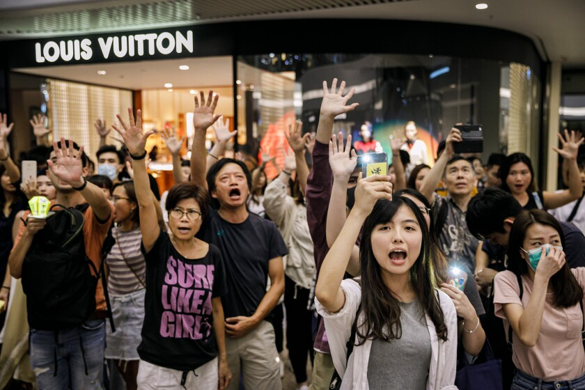 "Protesters chant, ""Five demands, not one less,"" at Times Square Shopping Center, in Hong Kong."