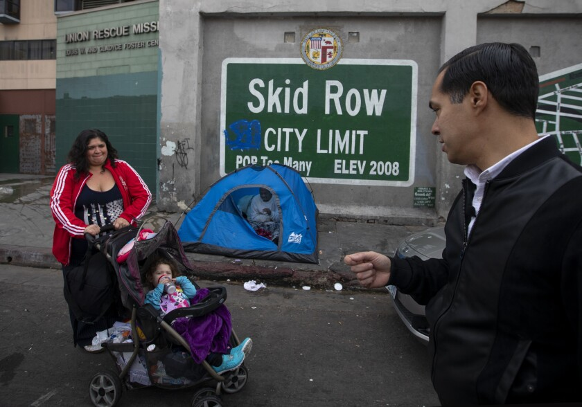 In front of a small tent pitched on L.A.'s skid row, a woman and child are approached by a politician