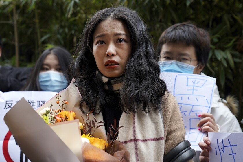 Zhou Xiaoxuan, center, speaks to supporters holding banners as she arrives at court in Beijing.